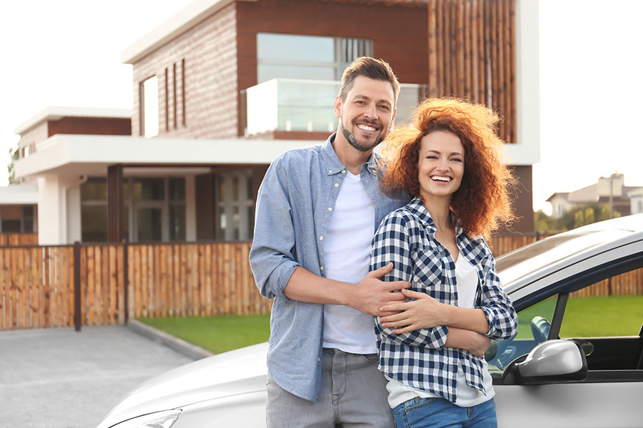Auto Insurance - Couple Holding Each Other Standing by Car with House in Background