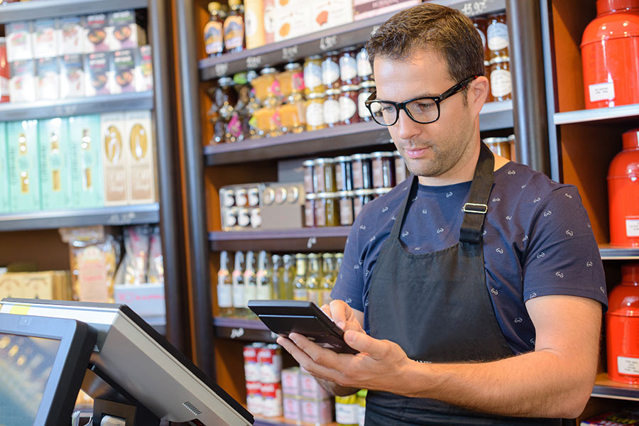 Business Owners insurance - Man with Apron Holding Ipad in Store
