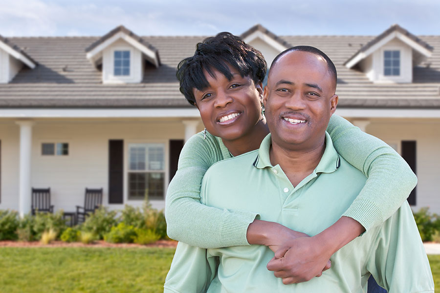 Home Insurance - African American Couple Hugging with House in Background